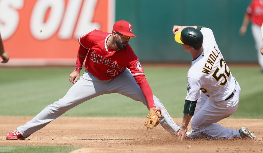 Oakland Athletics' Joey Wendle slides past Angels' Kaleb Cowart to steal second base in the third inning Wednesday.