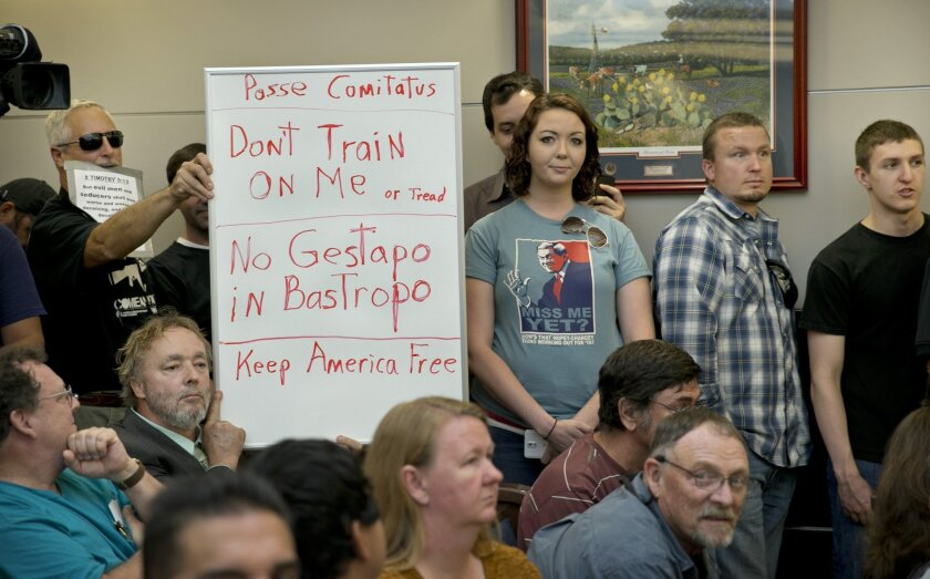 Bob Welch, standing at left, and Jim Dillon, hold a sign at a public hearing last April about the Jade Helm 15 military training exercise in Bastrop, Texas.