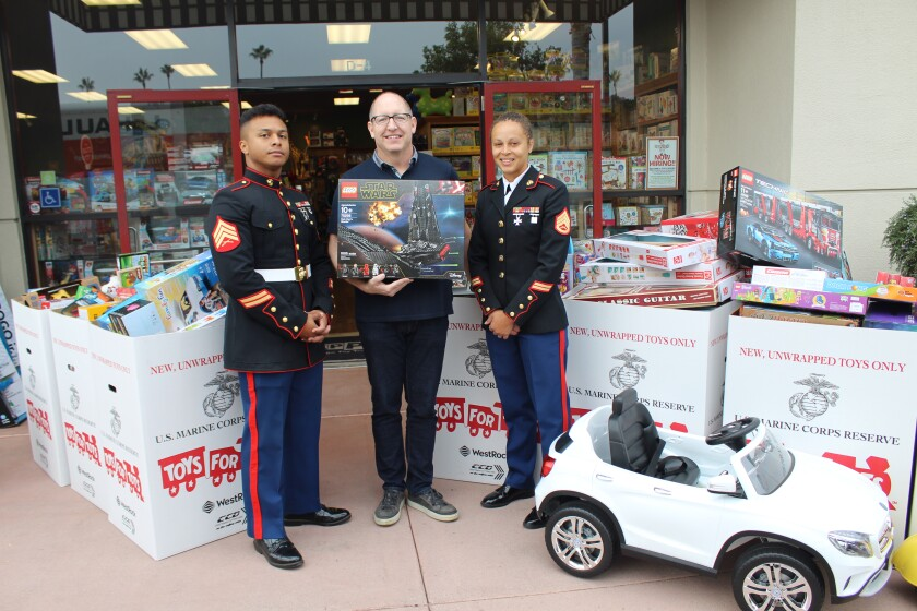 Marine Sgt. Davian Rima, Geppetto's owner Brian Miller and Staff Sgt. Dominique Williams with the donations to Toys for Tots.