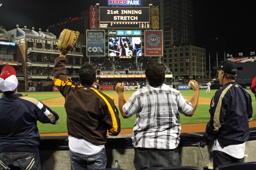 """Most fans had left but those who were still there after midnight take a """"21st Inning Stretch"""" at Petco Park."""
