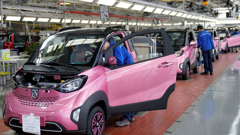 FILE PHOTO: Workers inspect Baojun E100 all-electric battery cars at a final assembly plant operated by General Motors Co and its local joint-venture partners in Liuzhou