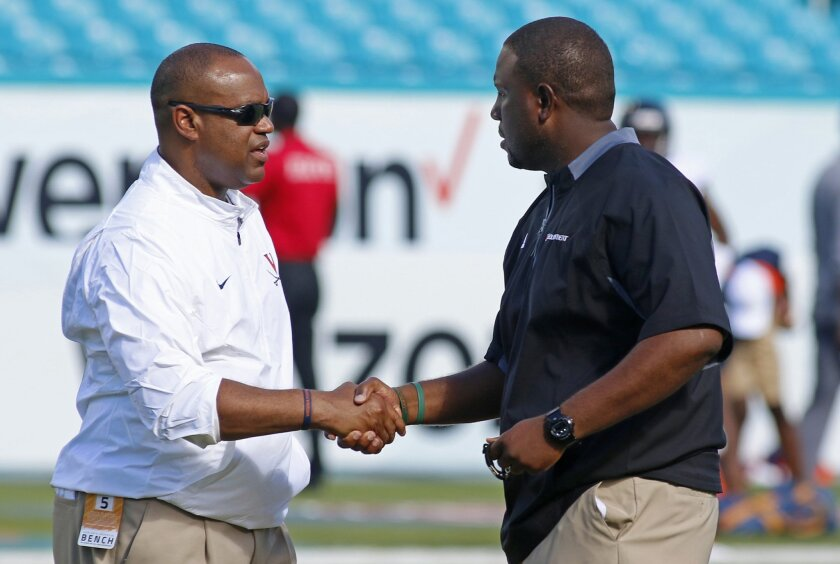 Virginia head coach Mike London, left, shakes hands with interim Miami head coach Larry Scott before their teams met in an NCAA college football game, Saturday, Nov. 7, 2015, in Miami Gardens, Fla. (AP Photo/Joe Skipper)