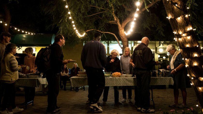 MALIBU, CA - NOVEMBER 15: People line up as volunteers serve food at Malibu United Methodist Church