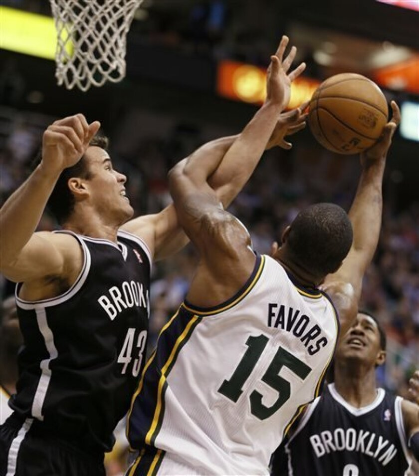 Brooklyn Nets' Kris Humphries, left, fight for a rebound with Utah Jazz's Derrick Favors during the first half of an NBA basketball game, Saturday, March 30, 2013, in Salt Lake City. (AP Photo/George Frey)