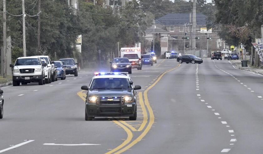 Police cars escort an ambulance