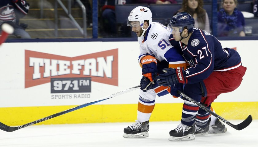 New York Islanders' Frans Nielsen, left, of Denmark, and Columbus Blue Jackets' Ryan Murray chase a loose puck during the first period of an NHL hockey game Tuesday, Feb. 9, 2016, in Columbus, Ohio. (AP Photo/Jay LaPrete)