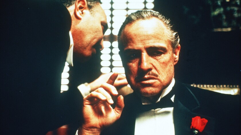 "Salvatore Corsitto whispers to Marlon Brando in ""The Godfather."""