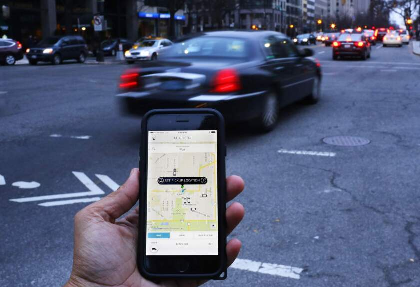 Who gets the benefit?This file photo shows the Uber smartphone app, being used by a passenger in Washington, D.C.