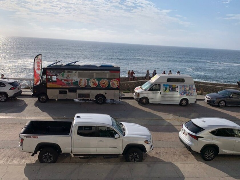 A food truck and an ice cream truck are pictured parked on Coast Boulevard near the Children's Pool in La Jolla.