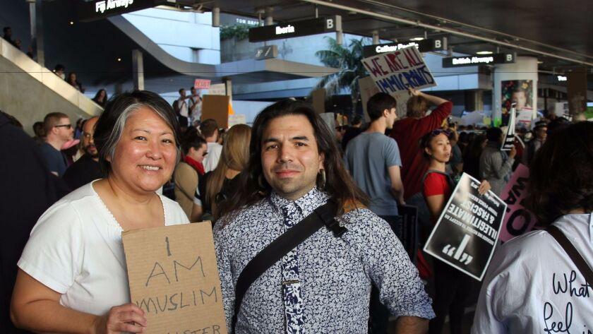 Arts writer Carol Cheh and artist and administrator Marshall Astor protest Trump's travel ban at Tom Bradley International Terminal at LAX.