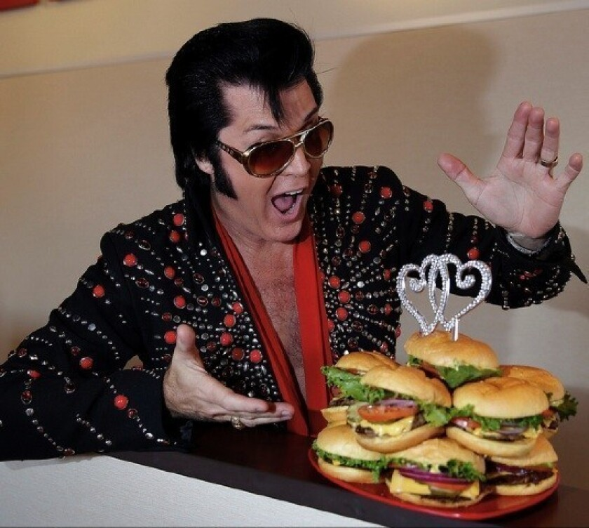 """Elvis, really Brendan Paul from Graceland Chapel, officiated Tuesday at the Smashburger wedding in Las Vegas. The hamburgers formed a wedding """"cake."""""""