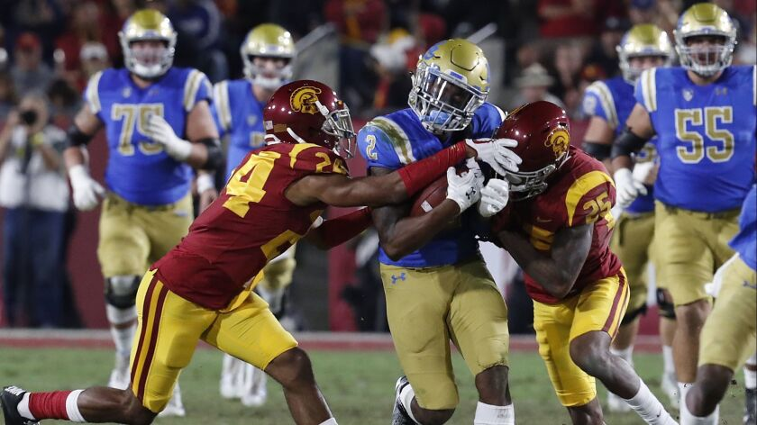 UCLA receiver Jordan Lasley is brought down by USC defenders Isaiah Langley, left, and Jack Jones after making a catch in the second quarter.