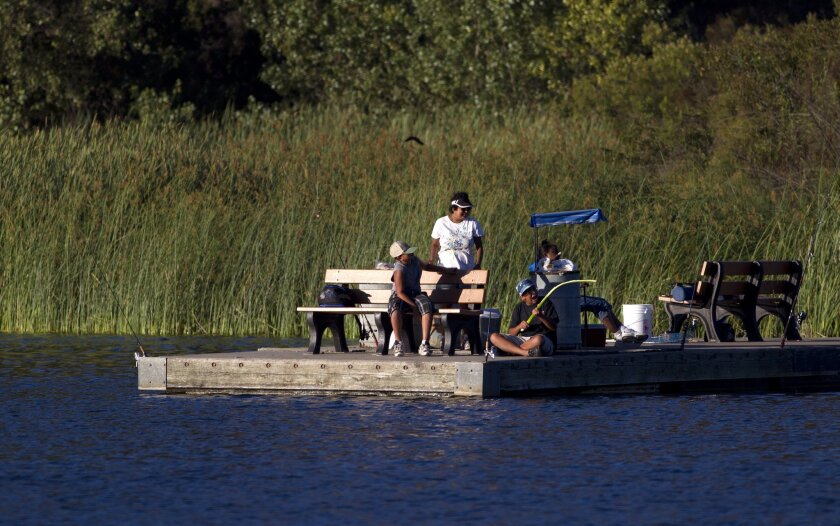 A family fishes during the night fishing Thursday night at Dixon Lake in Escondido.