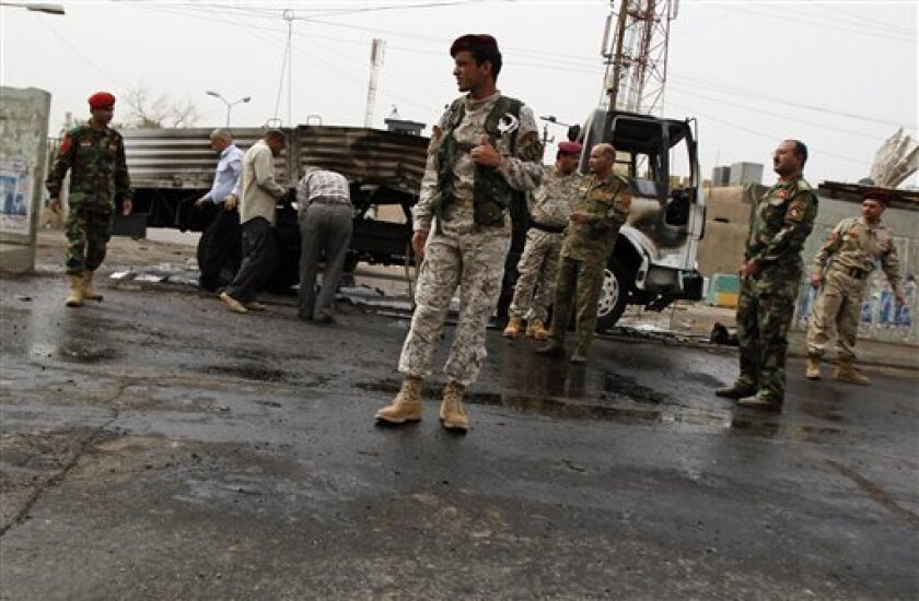 Iraqi security forces inspect a vehicle damaged in a roadside bomb blast in central Baghdad, Iraq, Sunday, May 10, 2009. A roadside bomb targeting a police patrol went off in central Baghdad's Karrada neighborhood, injuring four police officers. (AP Photo/Hadi Mizban)
