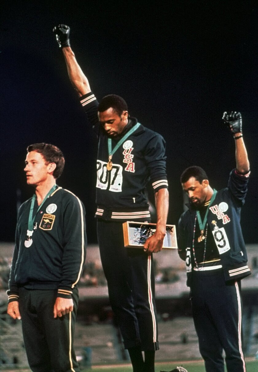 FILE - In this Oct. 16, 1968, file photo, extending gloved hands skyward in racial protest, U.S. athletes Tommie Smith, center, and John Carlos stare downward during the playing of the national anthem after Smith received the gold and Carlos the bronze for the 200 meter run at the Summer Olympic Games in Mexico City on. Australian silver medalist Peter Norman is at left. (AP Photo/File)