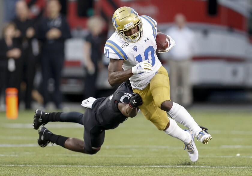 UCLA running back Demetric Felton breaks a tackle attempt by Cincinnati's Ja'von Hicks during the Bruins' loss on Thursday.