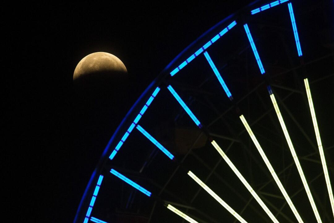 La metà inferiore della luna è oscurata dall'ombra della Terra vista da sotto la ruota panoramica al molo di Santa Monica