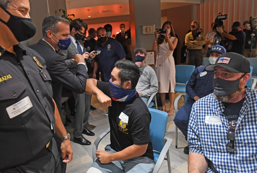L.A. City Firefighter Andrew Tom greets L.A. Mayor Eric Garcetti at a reunion for injured firefighters