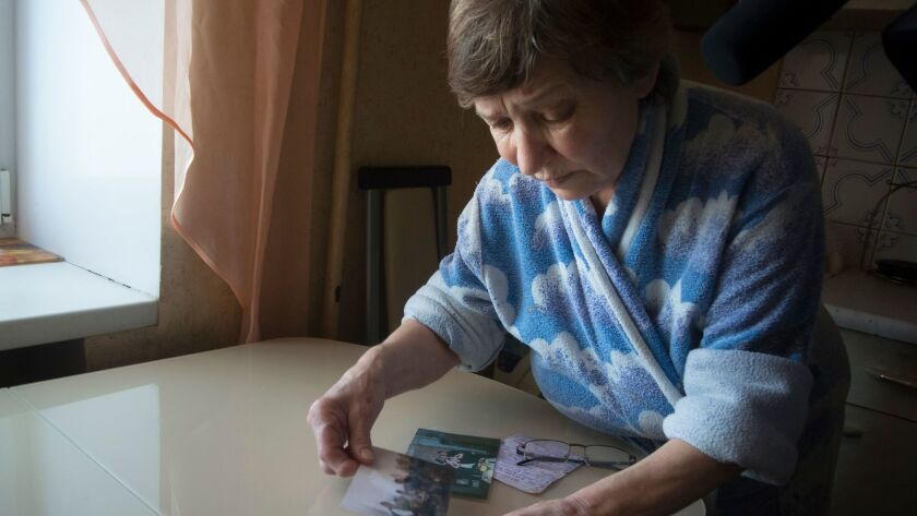 Farkhanur Gavrilova looks at photos of her son, Ruslan Gavrilov, in the village of Kedrovoye, Russia. He was one of seven men in the village who are believed to have joined a private military company called Wagner.