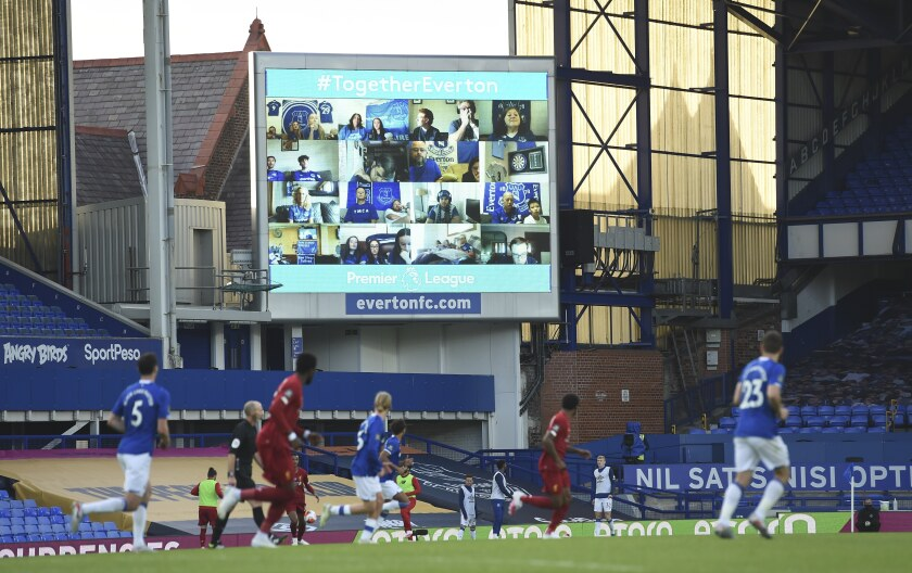 Everton fans are displayed on a large screen as the watch remotely the English Premier League soccer match between Everton and Liverpool at Goodison Park in Liverpool, England, Sunday, June 21, 2020. (Peter Powell/Pool via AP)