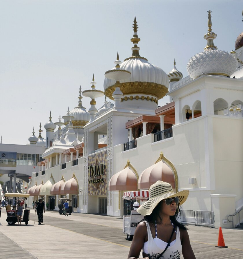 In this Wednesday, July 23, 2014 file photo, people walk on The Boardwalk past Trump Taj Mahal Casino Resort in Atlantic City, N.J. A Delaware bankruptcy judge on Friday, Oct. 3, 2014, denied a request by Trump Entertainment Resorts to be relieved of its pension obligations under a collective bargaining agreement with union workers at the Taj Mahal casino in Atlantic City. (AP Photo/Mel Evans, File)