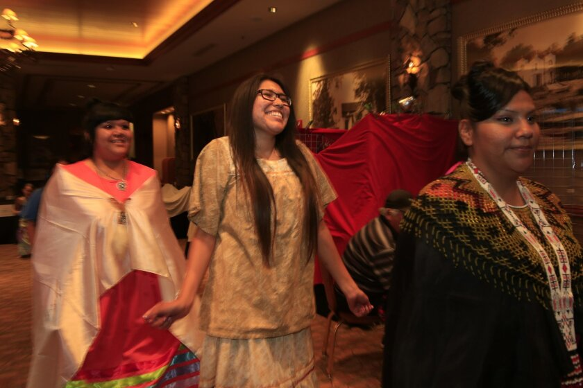 Melissa Hill, 19, from Viejas smiled as she entered the hall during a fashion show highlighting Native American clothing as part of the 13th Annual Yuman Language Family Summit. Hill made her dress to honor her Kumeyaay heritage. The event strives to maintain the language and culture of Native Americans.