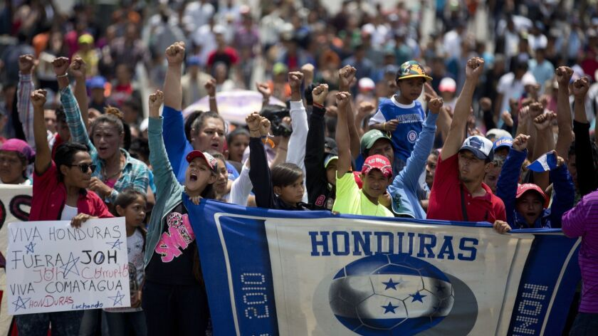Migrants from Honduras, who attended the annual Migrants Stations of the Cross caravan, shout slogan