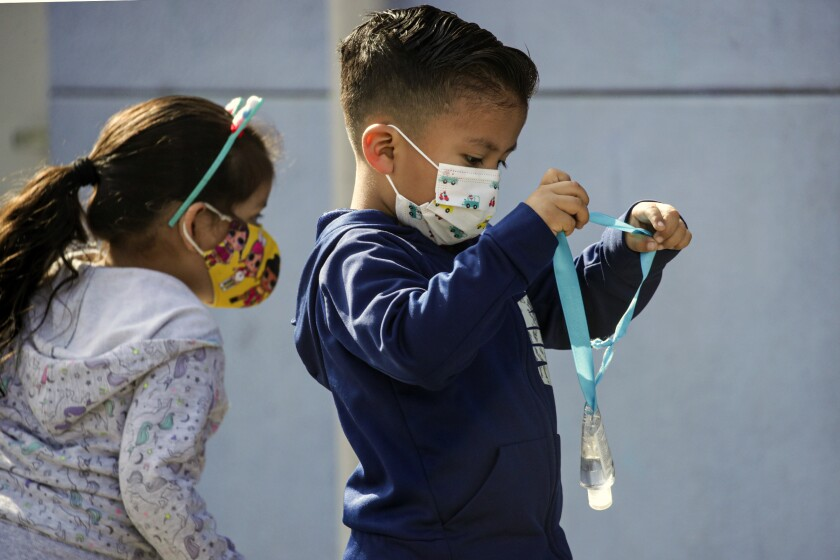 A boy wears face mask and carries a hand sanitizer bottle at Madison Elementary School  in South Gate.