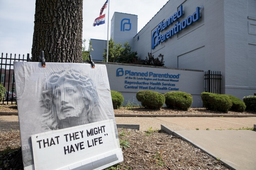 An abortion opponent's sign rests against a tree outside a Planned Parenthood clinic in St. Louis on