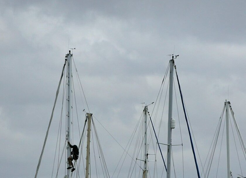 A sailor climbed down a mast of a sailboat yesterday as cloudy skies rolled in over the Chula Vista Marina in the South Bay. The beautiful weather earlier this week will give way to rain and lower temperatures today. A Pacific storm system is expected to bring snow showers and fog to mountain eleva