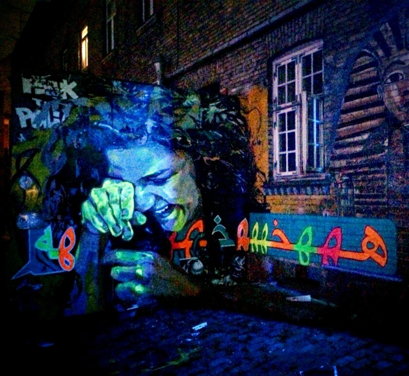 "This undated handout image provided by Egyptian artist Ammar Abo Bakr, shows graffiti titled ""Hahahaha"" painted on a wall by Abo Bakr depicting Egyptian activist Sanaa Seif, in Copenhagen, Denmark. When the 22-year-old Seif was summoned for questioning on accusations of inciting protests, she refu"