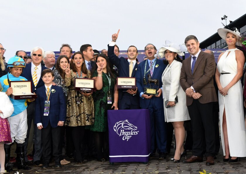 Jockey Victor Espinoza, left, Juan-Carlos Capelli, second right, VP and Head of International Marketing, Longines, and model and actress Kate Upton, right, celebrate with American Pharoah's owners and trainer Bob Baffert, second left, after American Pharaoh wins the Breeders' Cup Classic, at Keenel