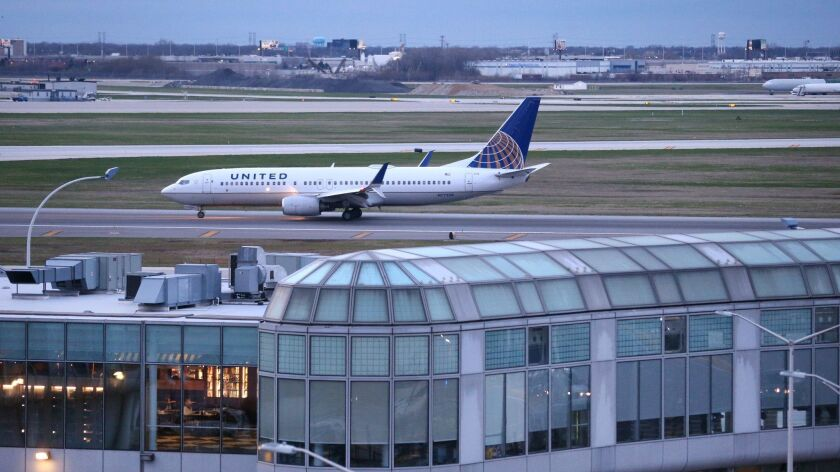 Terminal 1 is seen in the foreground as a United Airlines airplane rolls down the runway after landing at O'Hare Airport on April 11, 2017. (Chris Sweda/Chicago Tribune)
