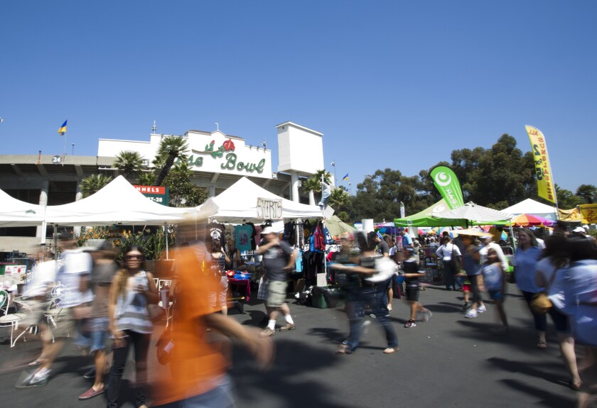 People walk back and forth among tents outside the Rose Bowl