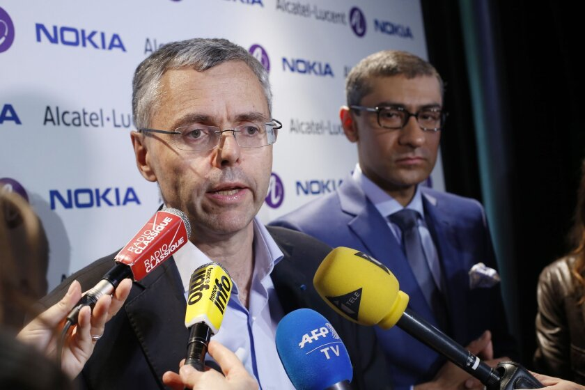 Alcatel-Lucent Chief Executive Michel Combes, left, and Nokia Chief Executive Rajeev Suri announce Nokia is buying its French rival.