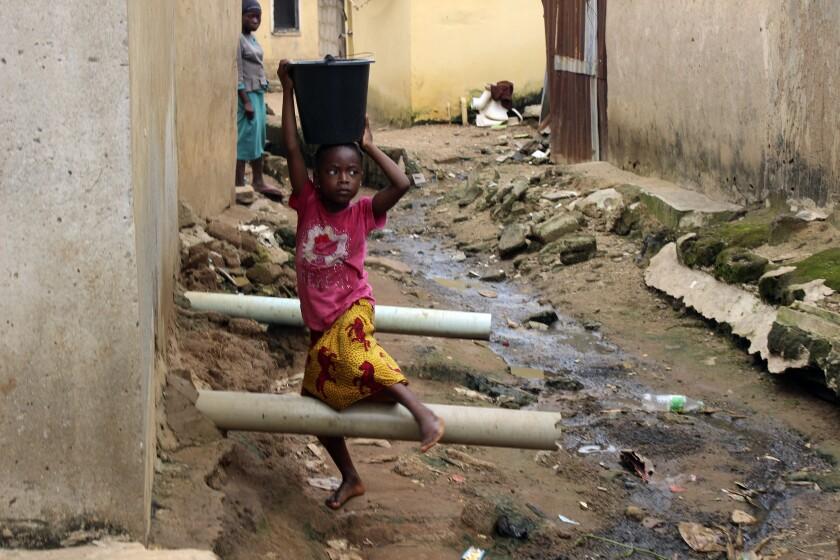 Una niña con agua sobre su cabeza pasa junto a aguas residuales entre las casas en Abuya, Nigeria
