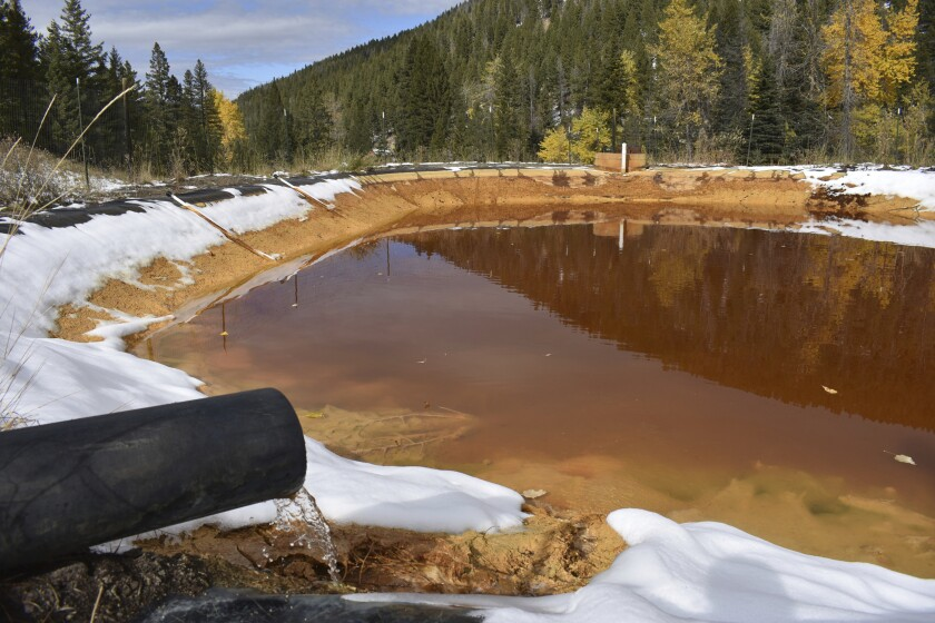 FILE - In this Oct. 12, 2018, file photo, water contaminated with arsenic, lead and zinc flows from a pipe out of the Lee Mountain mine and into a holding pond near Rimini, Mont. President Joe Biden's $2.3 trillion plan to transform America's infrastructure includes $16 billion to plug old oil and gas wells and clean up abandoned mines, a longtime priority for Western and rural lawmakers from both parties. (AP Photo/Matthew Brown, File)