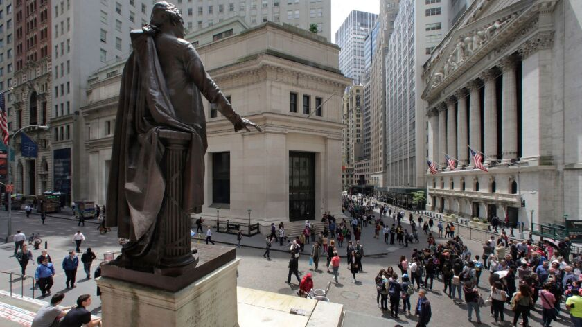 A statue of George Washington, on the steps of the Federal Hall National Monument, overlooks Wall Street and the New York Stock Exchange in May 2016.