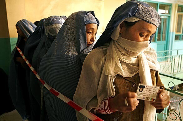 Holding their voter cards, women line up for balloting in Afghanistan, where the Taliban's threats of violence kept many away from the polls.