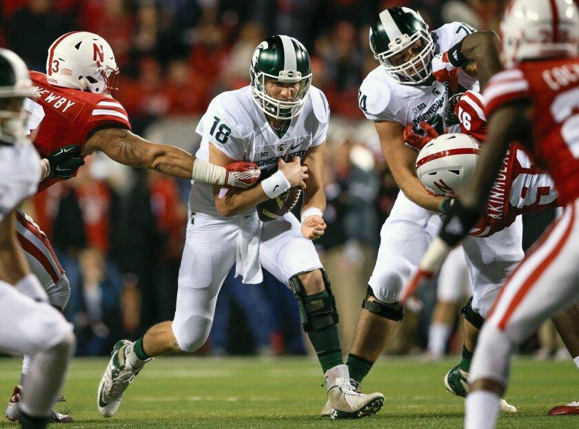 Michigan State quarterback Connor Cook (18) runs past Nebraska linebacker Marcus Newby during the first half of an NCAA college football game in Lincoln, Neb., Saturday, Nov. 7, 2015. (AP Photo/Nati Harnik)