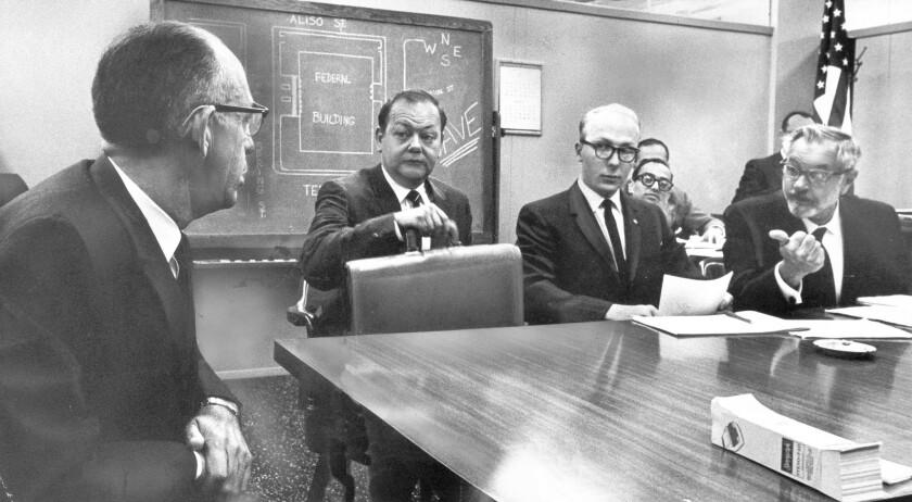 At his hearing, in July 1965, Michael Hannon, second from right, listens to testimony from then-Police Chief William H. Parker, left, over off-duty participation in civil rights and peace protests. He later became a lawyer.