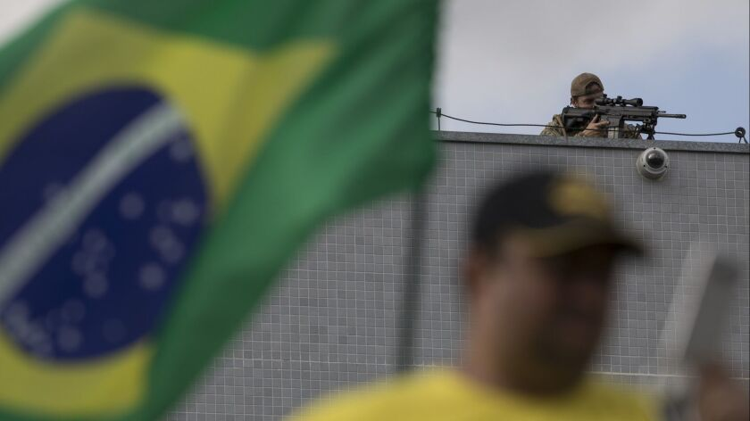 A federal police sniper aims his weapon as demonstrators protest against Brazil's former President L