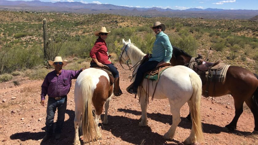 San Diego couple Kate and Michael Jackson enjoy the view with wrangler Jesse Schellhamer (left) on the trails at Rancho de los Caballeros.