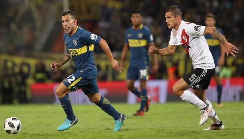 Carlos Tevez (i) de Boca Juniors controla el balón en el duelo contra River Plate durante la final de la Supercopa Argentina en el estadio Malvinas Argentinas en Mendoza (Argentina).