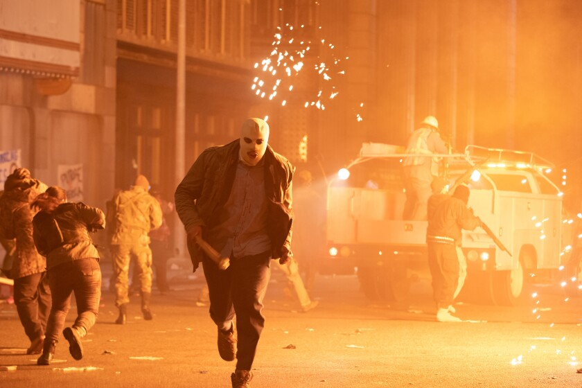 A masked figure carrying a bat runs down the street surrounded by acts of violence.