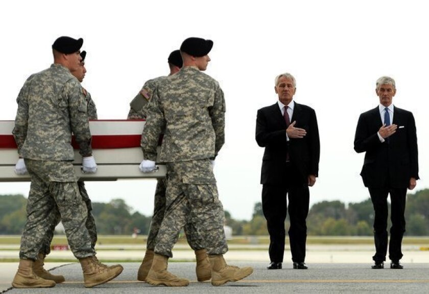 Secretary of Defense Chuck Hagel and Secretary of the Army John McHugh stand by as soldiers carry the flag-draped transfer case containing the remains of U.S. Army Pfc. Cody J. Patterson at Dover Air Force Base.