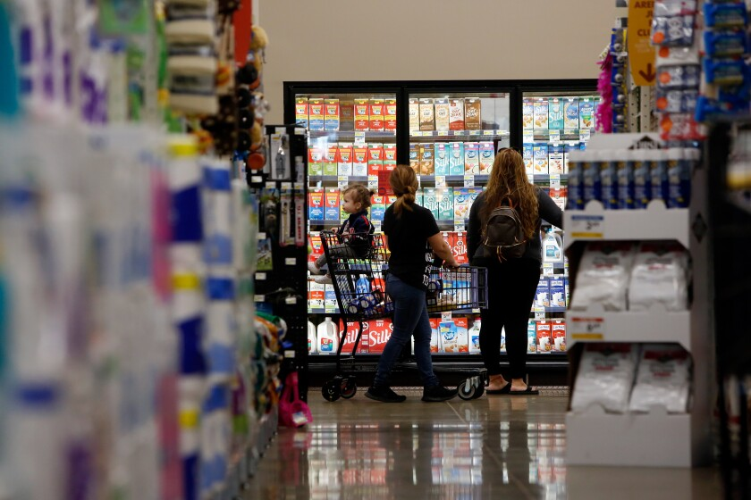 A baby sits in a cart as two women stop in front of the dairy case at a Smart & Final.