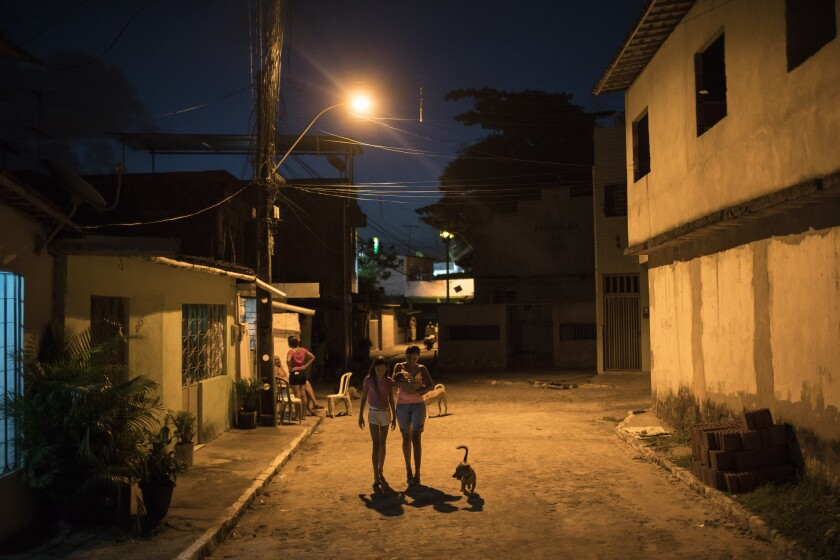 En esta imagen, tomada el 26 de enero de 2016, Daniele Ferreira dos Santos (centro) sostiene en brazos a su hijo Juan Pedro mientras camina junto a su hija mayor, Jennipher Karine, cerca de su casa en Recife, en el estado de Pernambuco, Brasil. En su quinto mes de embarazo, Daniele Ferreira dos Santos cayó enferma víctima de una fiebre alta y una serie de manchas rojas que invadieron su piel. Se recuperó pronto pero semanas más tarde, cuando fue al hospital a realizarse un examen prenatal, las noticias que recibió fueron tenebrosas: le dijeron que su bebé probablemente tenía una grave lesión cerebral. (Foto AP/Felipe Dana)