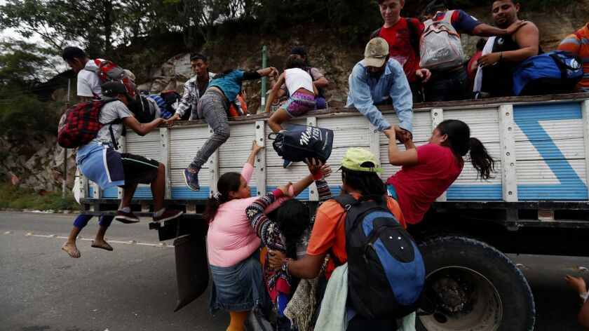 Honduran immigrants climb aboard a northbound truck in Guatemala in October 2018.