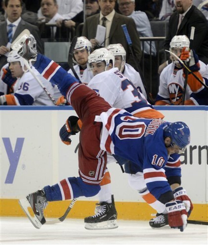 New York Islanders' Brian Strait, rear, sends New York Rangers' Marian Gaborik to the ice during the second period of an NHL hockey game at Madison Square Garden in New York, Thursday, Feb. 14, 2013. Strait was penalized two minutes for tripping. (AP Photo/Henny Ray Abrams)